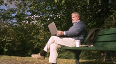 An elderly man with a computer in a park, Sweden. Arkistovideo