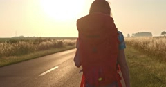 Traveler woman hitchhiking on a sunny road and walking. Young happy backpacker Stock Footage