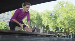 Female runner stretching her legs in slow motion Stock Footage