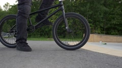 BMX biker puts feet on pedals close up Stock Footage