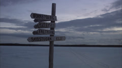 A signpost and a man on a snowmobile in the wilderness, Norrland, Sweden. Stock Footage