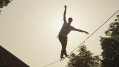 SLOW MOTION: Young man walking on slackline at golden sunset - stock footage