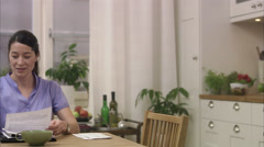 A man and a woman doing paper work at home, Sweden. Stock Footage