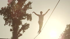 SLOW MOTION: Man walking on high slackline at summer sunset Stock Footage