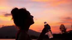 Sport Woman Drinking Water against Sunset Sky. Slow Motion Stock Footage