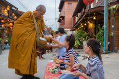 People put food offerings in a Buddhist monk's alms bowl for good merit - stock photo