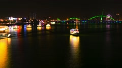Da Nang - May 2015: Night city view with Dragon Bridge, lotus flowers and boats. Stock Footage