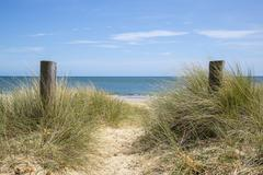 Lovely sand dunes and beach landscape on sunny Summer day Stock Photos