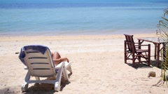 Woman Relaxing on Beach on Chaise Lounge on Holidays Stock Footage