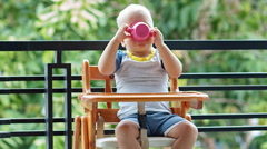 Toddler boy drinks a cup of yogurt and asks for more Stock Footage