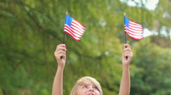 Little boy waving american flag in the park - stock footage