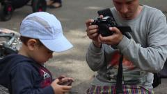 The operator with 4k camera changes position to capture a child with a mobile Stock Footage