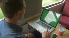 Young man sitting on the train using laptop with green screen Stock Footage
