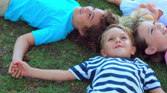Children lying on grass and smiling - stock footage