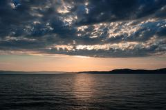 Tranquil sunset behind clouds over sea. - stock photo