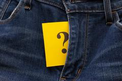 Yellow paper note with question mark appears out in jeans fly - stock photo