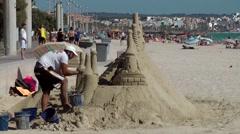 Spain Mallorca Island Playa de Palma 001 man builds a giant sandcastle at beach Stock Footage