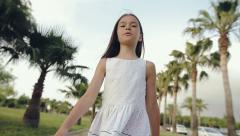 Child walks through a palm alley at sunset, rejoices and sings Stock Footage