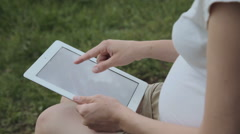 Pregnant woman using tablet pc in park Stock Footage
