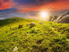 path through hillside with white boulders at sunset - stock photo