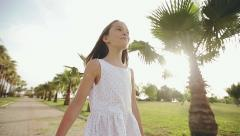 Child walks through a palm alley at sunset, rejoices and sings - stock footage