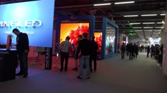 Stock Video Footage of 4k Fair visitors in LED video wall exhibition showroom hall