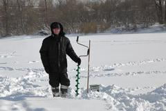Winter fisherman with ice screws on the river ice - stock photo