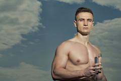 Attractive bodybuilder with glass of water - stock photo
