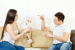 Young adult couple fight over stupid card game - stock photo