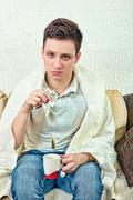 Young adult man treats himself with remedies - stock photo
