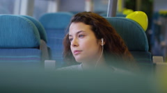 4k, tired female wearing earphones listening to music on a moving train Stock Footage
