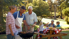 Happy man doing barbecue for his family - stock footage