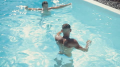Young guys splashing in a pool, having fun and diving Stock Footage