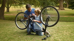 Father and his son fixing a bike in the park Stock Footage
