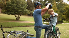 Father attaching his son cycling helmet in the park Stock Footage