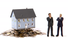 A miniature house is taken away from a leap of coins. Stock Footage