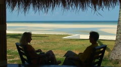 Romantic couple sitting on the bench near the beautiful sea and the beach Stock Footage