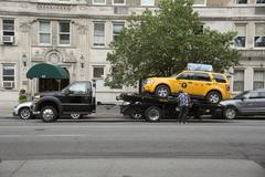 Broken down New York taxi getting trailered away - stock photo