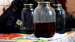 The girl fills the half-full bottle of dark red compote Stock Footage
