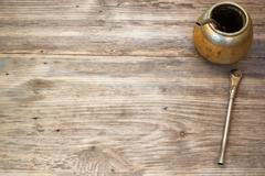 Calabash and bombilla with yerba mate on wooden background. Copy space to rig - stock photo