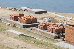 Red bricks stacked in piles at the construction site - stock photo