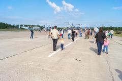 People walk between the planes at the open day at the aerodrome Migalovo - stock photo