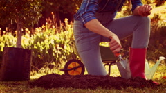Woman digging soil and planting flower Stock Footage