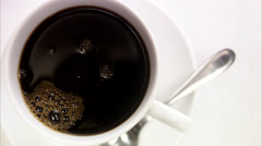Adding a lump of sugar to a cup of coffee. Stock Footage