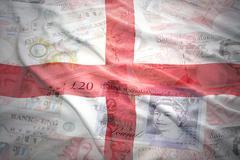 Colorful waving english flag on a english pound sterling money background Kuvituskuvat