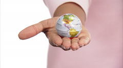 A small terrestrial globe in the hands of a woman, close-up. Stock Footage