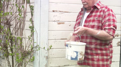Elderly man painting his summer cottage, Sweden. Stock Footage