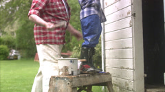 Grandfather and grandson painting their summer cottage, Sweden. Stock Footage