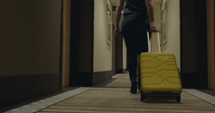 Woman with trolley bag looking for room in hotel Stock Footage