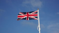 British flag waving in the wind against a clear blue sky,very windy,bird passes Stock Footage
